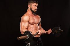 El atleta de sexo masculino muscular está entrenando levantando el barbell Fotografía de archivo libre de regalías