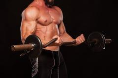 El atleta de sexo masculino muscular está entrenando levantando el barbell Imagenes de archivo