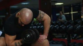 El atleta de sexo masculino muscular tatuado que hace pesa de gimnasia ejercita, resolviéndose en gimnasio almacen de video