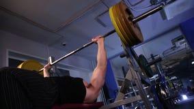El atleta de sexo masculino realiza la prensa de banco del barbell 140kg Deslice la cantidad de la leva almacen de metraje de vídeo