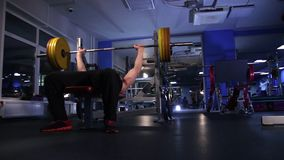El atleta de sexo masculino realiza la prensa de banco del barbell 140kg Fondo azul marino Deslice la cantidad de la leva almacen de metraje de vídeo