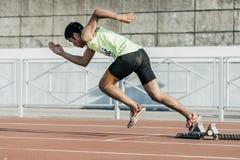El atleta de sexo masculino sale de bloques el comenzar en una distancia de 400 metros Imagen de archivo libre de regalías
