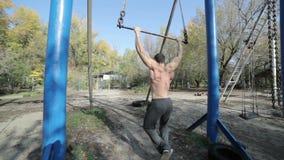 El atleta de sexo masculino se tira para arriba en la barra transversal almacen de video