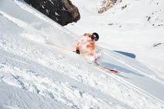 El atleta del esquí en un polvo fresco de la nieve acomete abajo de la cuesta de la nieve Imágenes de archivo libres de regalías