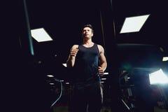 El atleta del hombre corre activar en una rueda de ardilla en gimnasio oscuro Imágenes de archivo libres de regalías