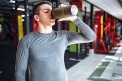 El atleta del hombre tomó una rotura en el entrenamiento y el agua potable, con una botella de los deportes en el gimnasio imagenes de archivo