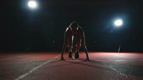 El atleta delgado de la chica joven está en la posición a comenzar a correr en los cojines en la pista en la cámara lenta metrajes