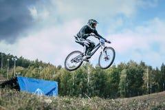 El atleta en una bici de montaña está volando en un salto de un trampolín Imagen de archivo libre de regalías