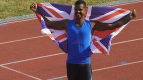 El atleta feliz que sostiene la bandera de su país en manos, Gran Bretaña es orgulloso de ganador almacen de video
