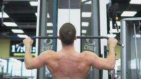 El atleta hace los ejercicios para los músculos de la parte posterior Parte posterior muscular del culturista en el dispositivo e almacen de video
