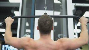 El atleta hace los ejercicios para los músculos de la parte posterior Parte posterior muscular del culturista en el dispositivo e metrajes