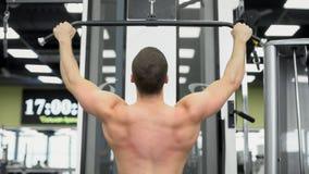 El atleta hace los ejercicios para los músculos de la parte posterior Parte posterior muscular del culturista en el dispositivo e fotografía de archivo libre de regalías