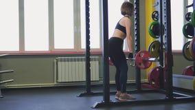 El atleta hace un ejercicio difícil con la elevación de una pesa de gimnasia en una mitad-posición en cuclillas almacen de metraje de vídeo