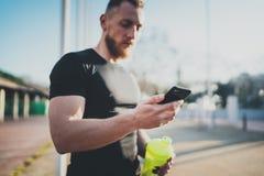El atleta hermoso muscular que comprueba deporte resulta en el uso del smartphone y el reloj elegante después de la buena sesión  Fotografía de archivo