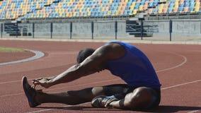 El atleta hispánico que calienta el suyo detrás, haciendo flexibilidad ejercita en circuito de carreras almacen de video