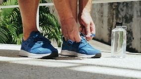 El atleta implica las zapatillas de deporte del azul de los cordones almacen de metraje de vídeo
