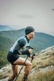 El atleta joven con los polos que caminan del nordic está en el lado de la montaña Imagen de archivo libre de regalías