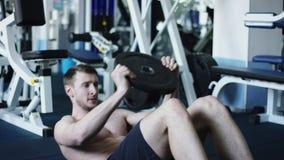 El atleta joven ejercita su ABS con los pesos en un gimnasio con el torso desnudo metrajes