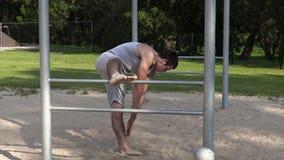 El atleta joven hace estirar ejercicios en barras almacen de video