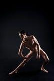 El atleta joven implicado que estiraba en el negro coloreó el estudio imagen de archivo libre de regalías