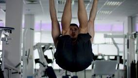 El atleta joven levanta sus piernas en una barra transversal en un gimnasio almacen de metraje de vídeo