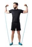 El atleta joven que hace los brazos y los hombros ejercitan con las bandas elásticas del caucho de la resistencia Imágenes de archivo libres de regalías