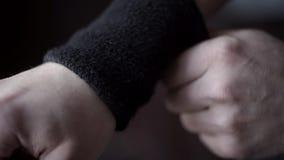El atleta lleva pulseras negras acci?n El primer del atleta ajusta sus pulseras en sus manos, para no dañar la muñeca durante almacen de video