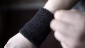 El atleta lleva pulseras negras acci?n El primer del atleta ajusta sus pulseras en sus manos, para no da?ar la mu?eca durante almacen de video