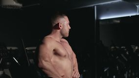 El atleta muestra sus músculos almacen de video