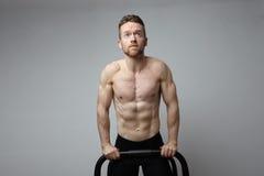 El atleta muscular descamisado que hace el pectoral encendido empuja hacia arriba barras Fotografía de archivo