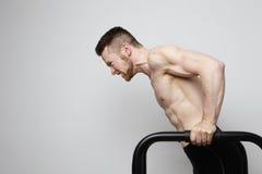 El atleta muscular descamisado que hace el pectoral encendido empuja hacia arriba barras Foto de archivo