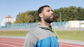 El atleta negro con una barba en un traje de los deportes va al aire libre almacen de metraje de vídeo