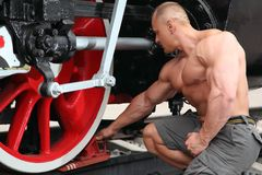 El atleta pone el cargador del programa inicial del freno bajo la rueda locomotora Foto de archivo