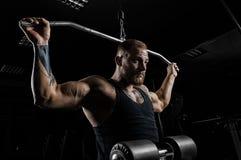 El atleta profesional realiza un ejercicio en el gimnasio Tira de fotografía de archivo