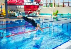 El atleta profesional salta en el agua en la piscina Imagen de archivo