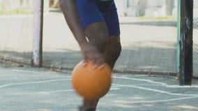 El atleta que juega al baloncesto, bola de goteo hábilmente para puentear al opositor, se divierte almacen de video