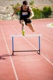 El atleta que salta sobre el obstáculo Foto de archivo