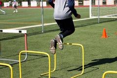 El atleta que salta sobre obstáculos amarillos Imagen de archivo