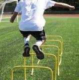 El atleta que salta sobre obstáculos amarillos en un campo verde del césped Fotos de archivo