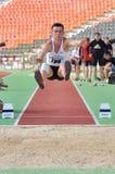 El atleta salta en el hoyo con la arena Fotografía de archivo