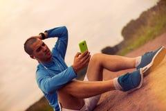 El atleta serio mira smartphone después de entrenar y de estudiar Fotografía de archivo