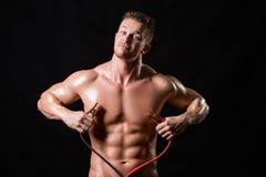 El atleta sostiene los alambres de alto voltaje imagenes de archivo
