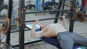 El atleta un culturista aumenta un barbell hecho a sí mismo almacen de metraje de vídeo