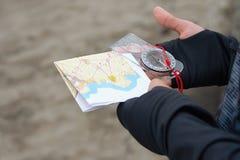 El atleta utiliza el equipo de la navegación para orienteering, el compás y el mapa topográfico Fotografía de archivo