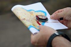 El atleta utiliza el equipo de la navegación para orienteering, el compás y el mapa topográfico Imagen de archivo