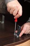El atornillar atornilla con un destornillador de la mano, monta la colocación de los muebles Imagen de archivo