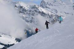 El atravesar de tres esquiadores Imagenes de archivo