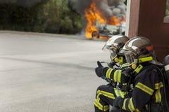 El attac binomial del bombero francés en el fuego del coche dice muy bien imagen de archivo