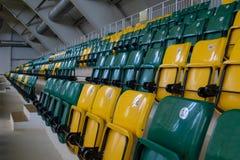 El auditorio en el complejo de los deportes con los asientos pl?sticos verdes y amarillos Los lugares para los espectadores del l imagen de archivo libre de regalías