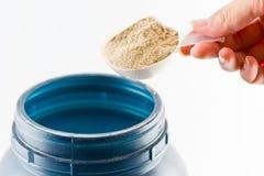 El aumento de la mano un polvo del chocolate de la proteína de la medida de la cuchara para Fotos de archivo libres de regalías